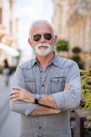 Old rich man with sun glasses and beard on street portrait