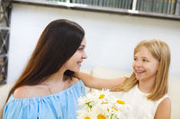 Little girl giving bouquet of beautiful flowers to her mother