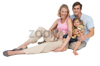 Happy young family expecting a new arrival smiling at camera