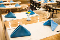 Row of empty dinner tables in restaurant