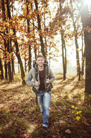 Young man with a backpack travels through the autumn forest on a sunny warm day. Smiling Caucasian tourist walks in nature. Hiking concept