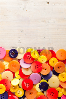 A pile of colorful buttons with copy space on wood