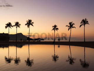 Sunrise over ocean with palm trees