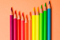 The colored pencils are arranged in rainbow colors closeup
