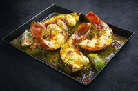 Traditional barbecue spiny lobster tail sliced and offered with saffron lemon sauce as closeup in a metal tray