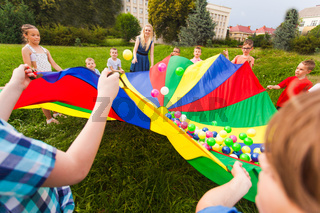 Kids holding rainbow parachute with colorful balls on it