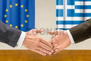 Representatives of the EU and Greece shake hands
