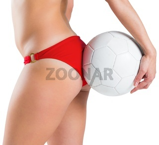 Fit girl in bikini holding football