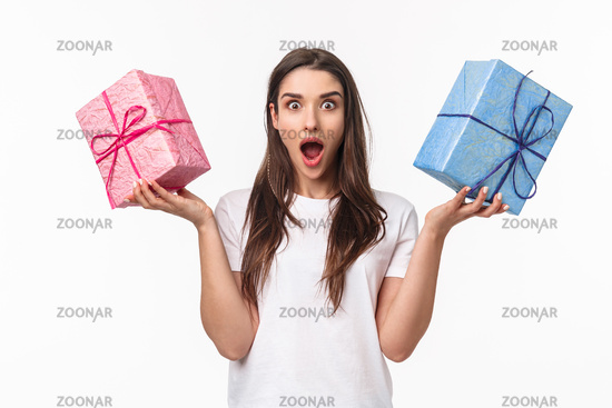 Celebration, holidays and presents concept. Portrait of excited and astounded, amazed young girl receive two awesome wrapped gift boxes, wander whats inside, stand white background surpised