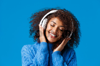 Close-up portrait happy smiling, romantic and tender african american woman enjoying listening music in headphones, tilt head close eyes dreamy and grinning delighted, blue background