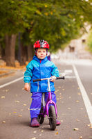 Boy in warm jacket siting on his balance bike