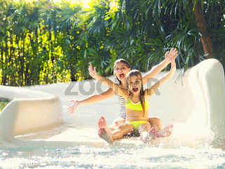 Cute little girsl on water slide at a vacation resort