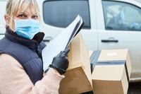 Paketbotin mit Mundschutz überprüft Lieferung auf Liste