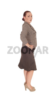 Business woman standing in a jacket and skirt in profile
