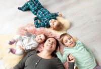 Top view of beautiful young mother, their cute little daughter and two son, lying on wooden floor.