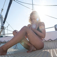 Beautiful woman relaxing on a summer sailing cruise, sitting and sunbathing in hammock of luxury catamaran sailing around Maddalena Archipelago, Sardinia, Italy in warm afternoon light