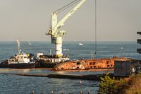 Oil tanker Delphi crashed near Black Sea coast in Ukraine, Odessa 26 August 2020. Small tanker, rusty old, lies on its side in sea. Lifting sunken ship with crane tug. Shipwreck disaster tanker Delfi