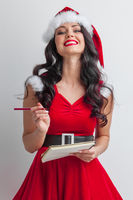 Santa girl with wish list and pencil