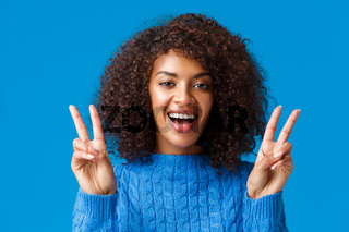 Charismatic excited and happy, smiling cheerful african american woman sending positive vibes, showing peace gesture and grinning, enjoying winter holidays, new year party, say cheese