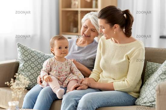 mother, daughter and grandmother on sofa at home