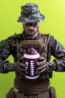 solder holding american football ball