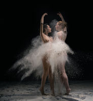 Naked dancers with raised arms in dust