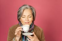 Charming adult woman drinks coffee holding white cup and closed eyes. Isolated on pink background. Studio shot. rest concept