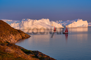 Greenland Ilulissat glaciers at ocean with red sailing boat
