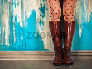 Female legs in brown leather boots near the wall