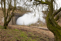 A cloud of stream from a restored steam train flows out of a tunnel on the re opened Gloucestershire Warwickshire Railway.