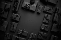 Arranged Gifts boxes wrapped in black paper with black ribbon on black background. Christmas concept