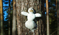 Snowman figurine on a tree trunk.