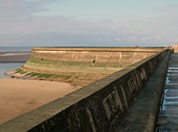 the seawall in blackpool with the beach at low tide in sunlight with the wall of the old boat pool