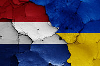 flags of Netherlands and Ukraine painted on cracked wall