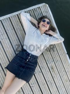 Stylish woman on pier near sea