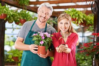 Mitarbeiter im Gartencenter mit Pflanze und Setzling