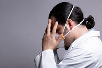 Frustrated medical doctor wearing a respiratory mask  touching his head with his hands. Burnout and medicine crisis concept.