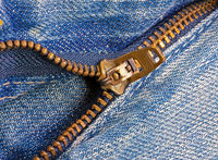 Open zipper of a worn out jeans