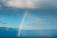 Rainbow coming out of cloud over ocean water