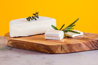 Pieces of camembert cheese on wooden cutting board