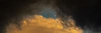 Panoramic view of dramatic storm clouds illuminated rising of sun floating in blue sky. Natural weather, meteorology background. Majestic cloudscape