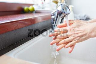 Seniorin beim Hände waschen mit Wasser und Seife