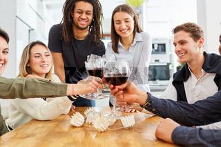 Gruppe Freunde auf einer Feier in der Küche stößt mit Glas Wein an