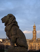 a lion sculpture in profile on the war memorial in Bradford city center with a view of the town hall and buildings form above