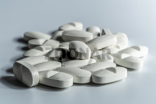 Closeup of many prescription drugs, medicine tablets or vitamin pills in a pile on white background - Concept of healthcare, opioids addiction, medicament abuse or medication treatment