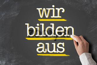 text WIR BILDEN AUS, German for we train apprentices, on chalkboard