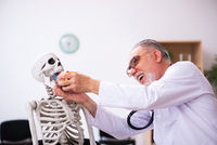 Old male doctor cardiologist and skeleton patient in the clinic