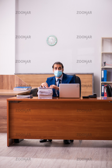 Young male employee working in the office wearing mask