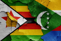 flags of Zimbabwe and Comoros painted on cracked wall