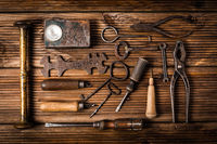 Collection of rusty tools and keys in vintage style on wooden background